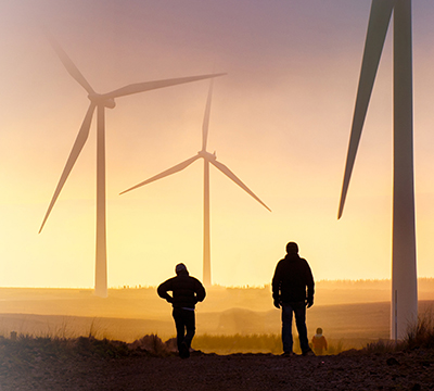 Two men in a field with wind turbines