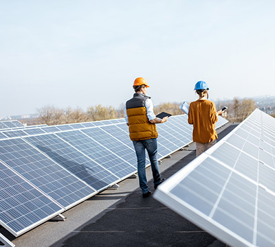 Two people with hard hats walking through an array of solar panels
