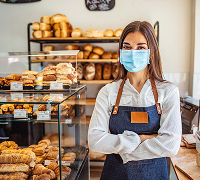 A bakery owner wearing a mask