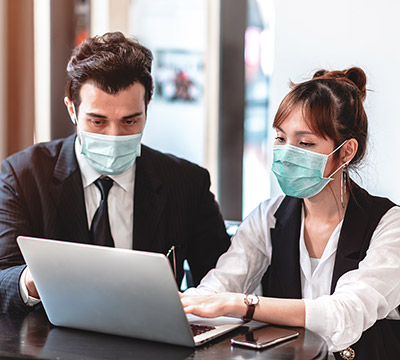 Two colleagues with masks in front of a laptop