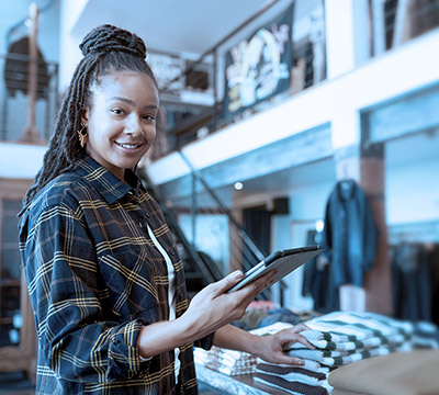 Female owner of fashion store using digital tablet to check stock in clothing store