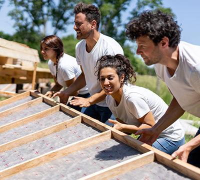 Four people helping lift the framing of a house