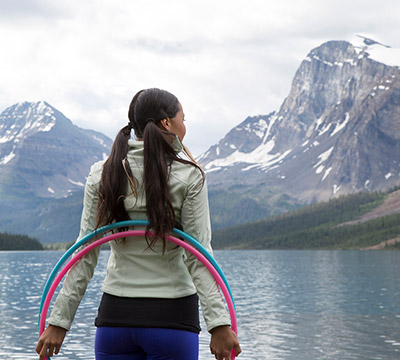 Indigenous woman standing by the lake with hula hoops