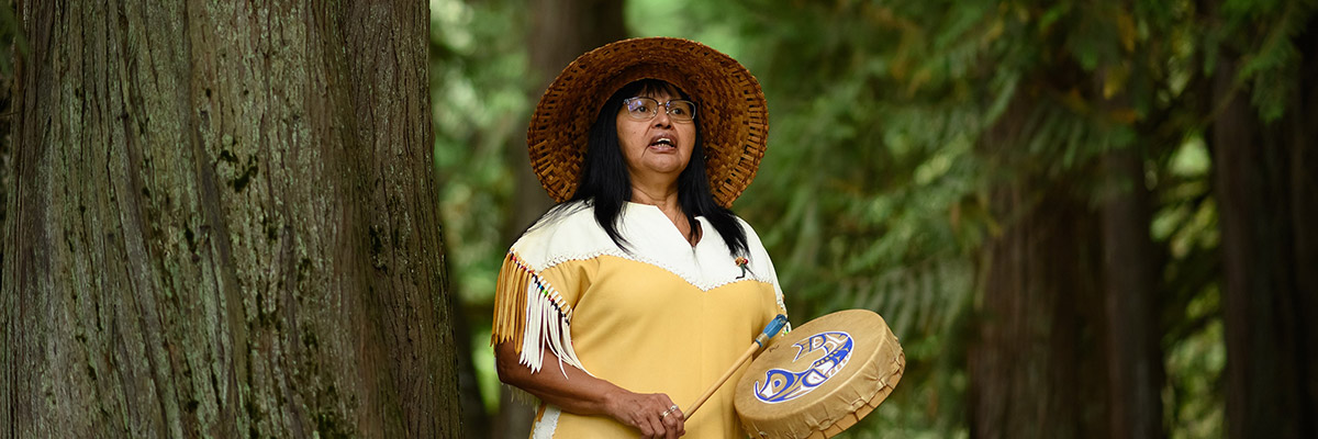 First Nations woman performing a traditional welcome song.