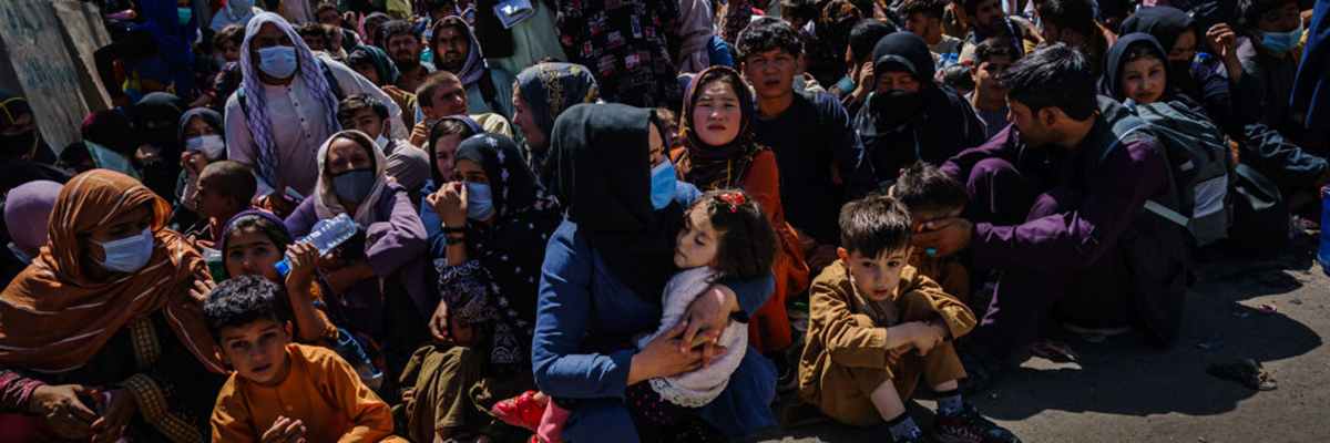 Women and children are made to crouch and wait outside the Taliban controlled check point near the Abbey Gate, before making their way towards the British military controlled entrance of the airport, in Kabul, Afghanistan