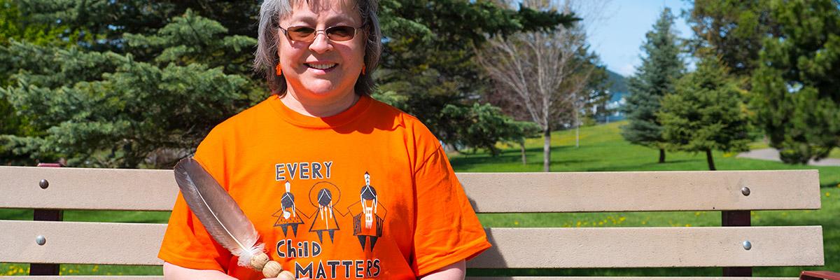 Phyllis Webstat wearing an orange shirt
